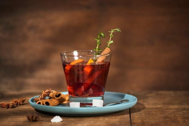 Herfstconcept met kopje thee met citroen, kaneelstokje en anijsster op rustieke houten muur
