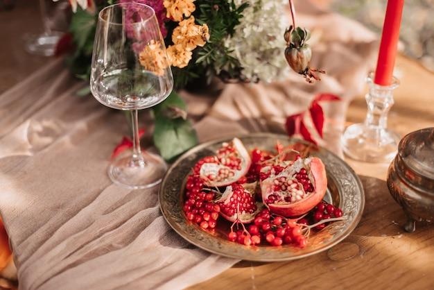 Herfstdecor: een boeket dahlia's, granaatappels, kaarsen, pompoenen en glazen