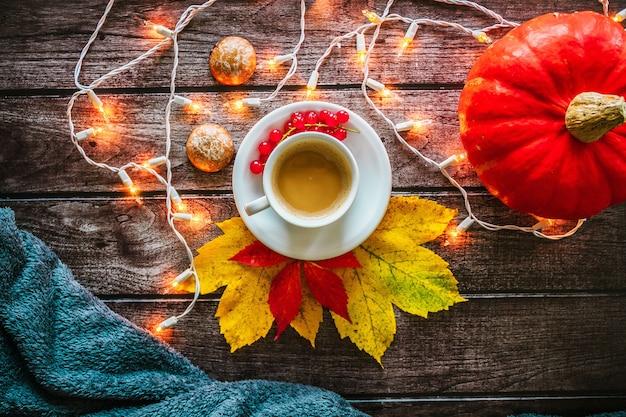 Herfstdecoratie kopje koffie met pompoen en plaid op een houten achtergrond gloeiende garland