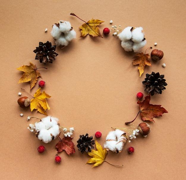 Herfstdecoratie met katoenen bloemen en droge esdoornbladeren in de vorm van een cirkel op een bruine achtergrond