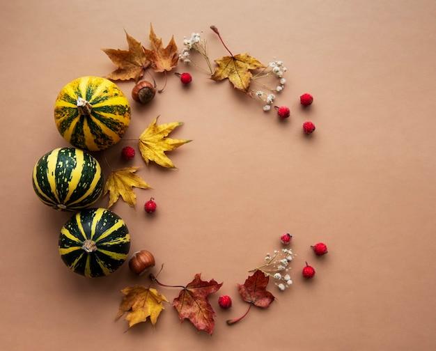 Herfstdecoratie met pompoenen en droge esdoornbladeren in de vorm van een cirkel op een bruine achtergrond