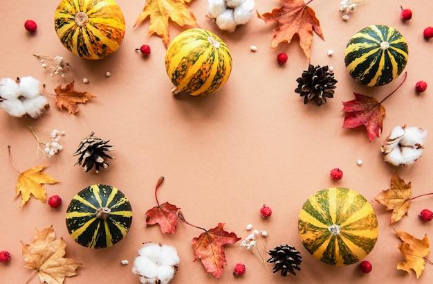 Herfstdecoratie met pompoenen en droge esdoornbladeren op bruin