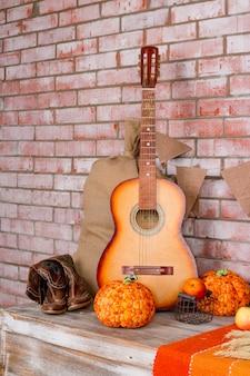Herfstdecoratie voor huis, feest, cowboylaarzen, pompoenen op bakstenen muur.