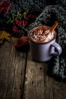 Herfstdranken, warme chocolademelk of cacao met slagroom en specerijen (kaneel, anijs), op de oude rustieke houten tafel, met een warme, gezellige deken, hooibes en blaadjes kopie ruimte