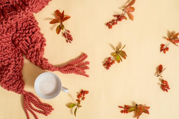 Herfstgerelateerde accessoires. oranje sjaal en muts gebreid van wollen garen. droge bladeren op een gele achtergrond. herfst kaart. gezellige lichte herfst t. plat lag, bovenaanzicht. kopie spase