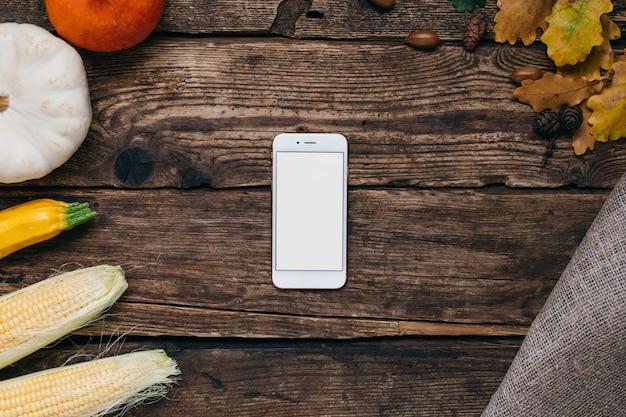 Herfstgroenten: mobiele telefoon met wit leeg scherm, pompoenen en maïs met gele bladeren op hout