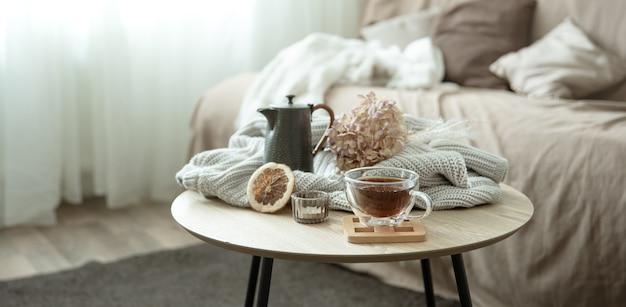 Herfsthuissamenstelling met een kopje thee, een theepot en een gebreid element.