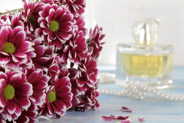 Herfstkleuren van chrysant en parfum op een blauwe houten tafel