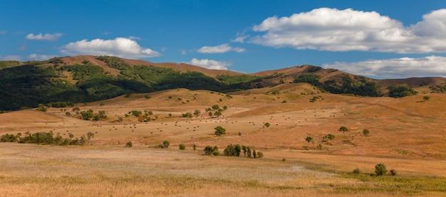 Herfstlandschap, heuvels tegen een blauwe hemel met wolken, een gemaaid veld met hooibergen aan de voet van de heuvels, panorama.