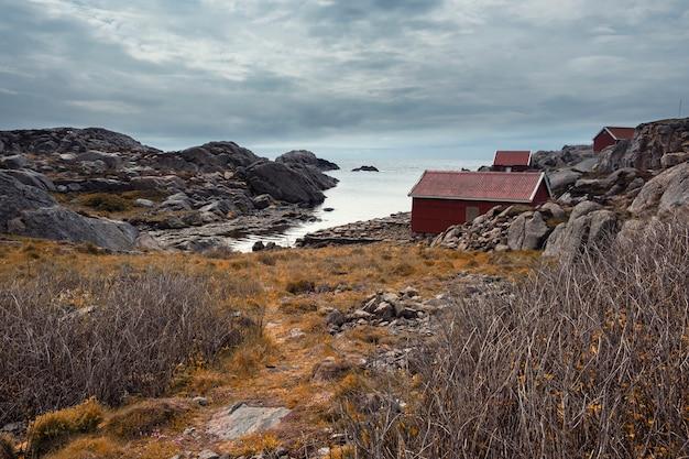Herfstlandschap in noorwegen. eenzaamheid met de natuur. traditionele rode houten hutten op de rotsachtige kust van de noordelijke zee