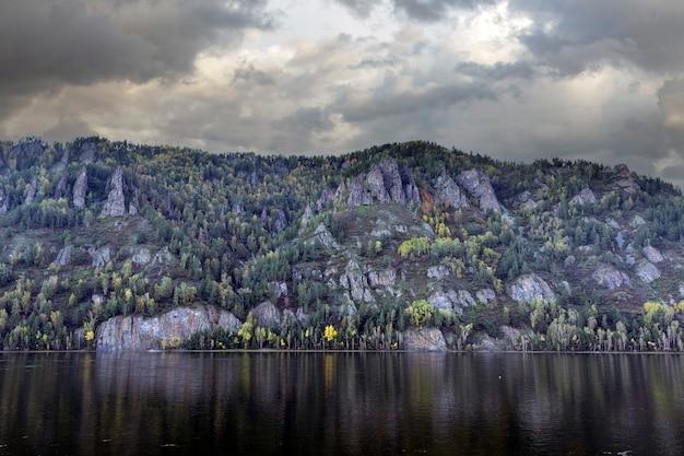 Herfstlandschap met troebele rivierhemel en bergen bedekt met bos