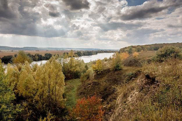 Herfstlandschap met uitzicht op de rivier door het bos en de rotsen