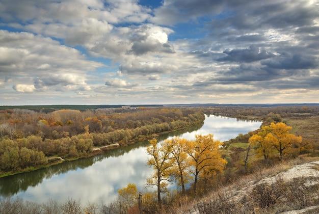 Herfstlandschap op de heuvels van de rivier de don. uitzicht op de vijver op een oppervlak van bewolkte hemel.