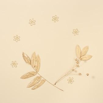 Herfstlay-out met bladeren van lijsterbes in gouden kleur op neutrale beige achtergrond