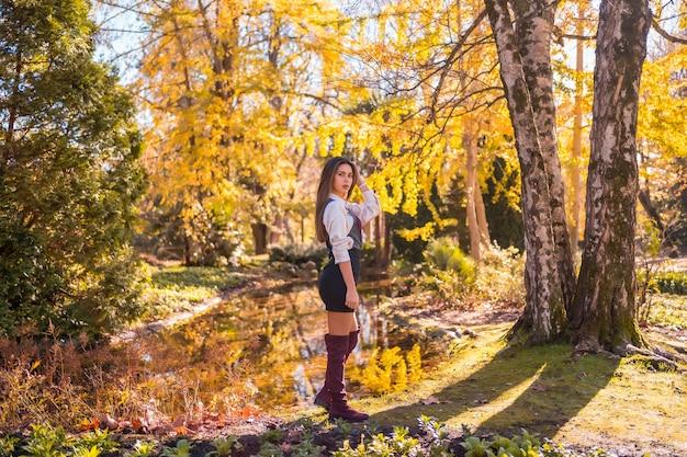 Herfstlevensstijl, een jonge blanke brunette, in een zwarte rok en kastanjebruine laarzen met een verleidelijke look, in een park aan een meer