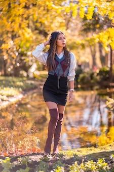 Herfstlevensstijl, een jonge blanke brunette, studente in een modieuze pose, in een park aan een meer