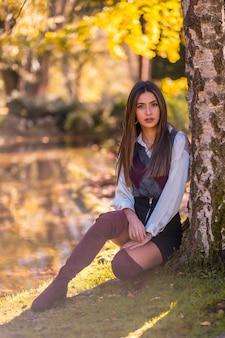 Herfstlevensstijl, een jonge brunette blanke, studente in een park naast een boom met een lachende blik
