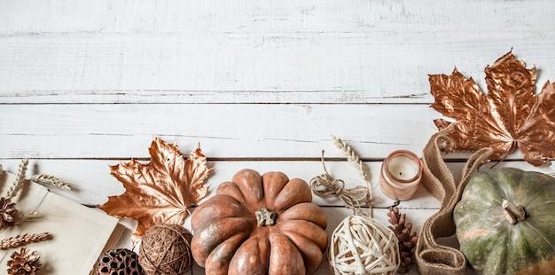 Herfstmuur met decoratieve voorwerpen en pompoen.