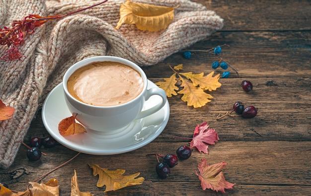 Herfstochtend een kopje koffie gebladerte en een trui op een houten achtergrond zijaanzicht ruimte om te kopiëren