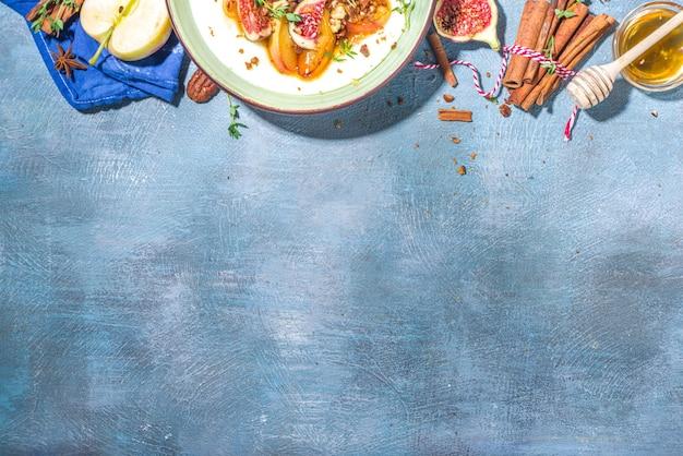 Herfstontbijt of -snack, pittige griesmeelpap met gekarameliseerde appels, gegrilde perzik, pruimen en vijgen, noot, tijm, honing. bovenaanzicht op blauwe, door de zon verlichte betonnen tafel