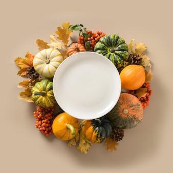 Herfstoogst van appel en kleurrijke bladeren en witte plaat in het midden met ruimte voor tekst