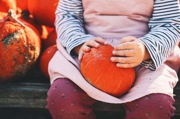 Herfstoogst van pompoenen kind plukt oranje pompoen op boerderijmarkt of seizoensfestival