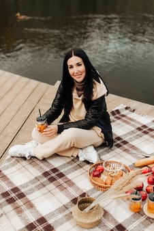 Herfstpicknick aan de oever stijlvolle brunette meisje zittend op een deken en kijken naar de camera