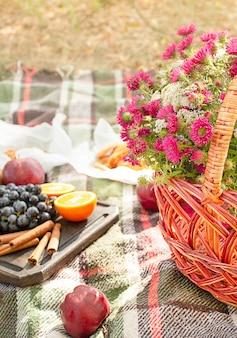 Herfstpicknick in het park, warme herfstdag. mand met bloemen op een deken. thee, croissants, koekjes, druiven in gele herfstbladeren. herfst concept.