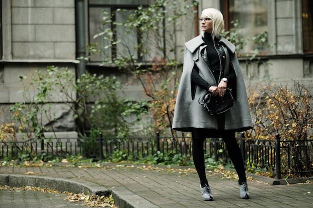 Herfstportret van mooie blonde vrouw in grijze jas met zwarte tas