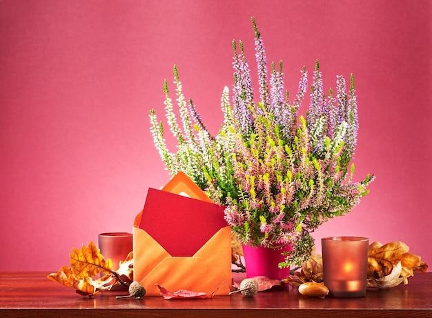 Herfstpost stilleven met wenskaart envelop heide bloemen in bloempot droge bladeren