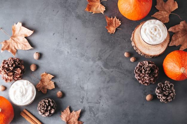 Herfstrand met natuurlijke dennenappels, pompoenen, gedroogde bladeren en pompoen latte op donkergrijze stenen top, bovenaanzicht, kopieerruimte. herfst, thanksgiving-achtergrond, gezellige platte lay