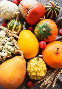 Herfstsamenstelling, gezellig herfstseizoen, pompoenen en bladeren op textielachtergrond. symbool van thanksgiving vakantie, plat lag