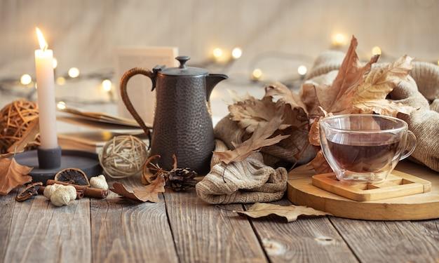 Herfstsamenstelling met een kopje thee en decoratieve artikelen. koud seizoen huiscomfort concept.