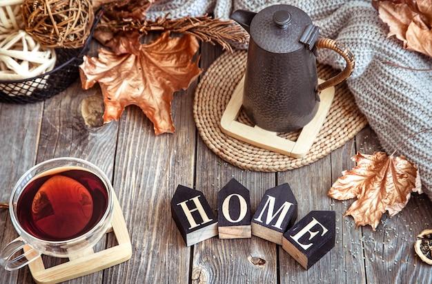 Herfstsamenstelling met een kopje thee, theepot en houten woord naar huis.