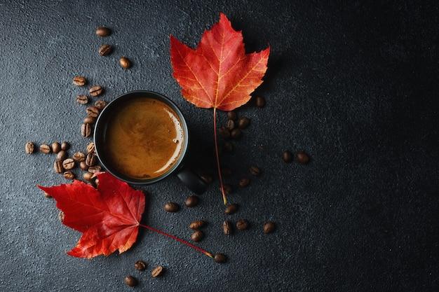 Herfstsamenstelling met vers gemaakte koffie in kop en esdoornbladeren