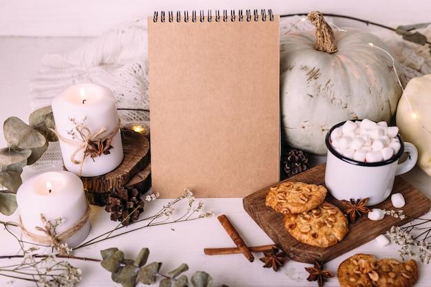 Herfstsamenstelling mockup cacao marshmallows koekjes pompoen en kaarsen