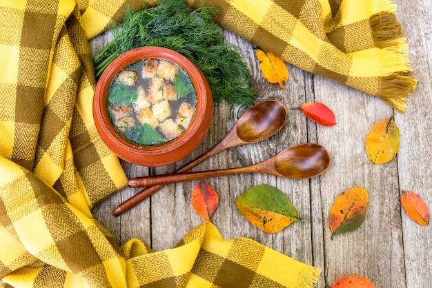 Herfstsoep in een pot en een gele fang-sjaal.