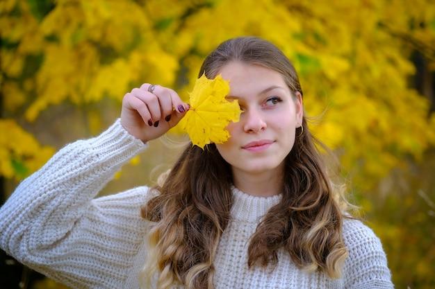 Herfststemming. een mooie jonge vrouw bedekt één oog met een geel herfstblad.