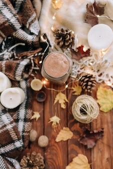 Herfststemming met bladeren, kaarsen, cacao, plaid. bovenaanzicht