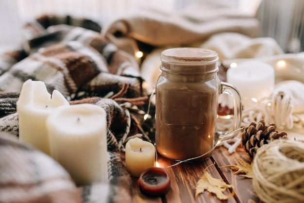 Herfststemming met bladeren, kaarsen, cacao