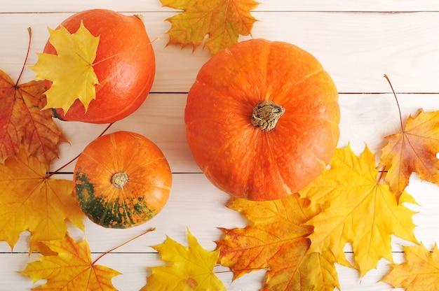 Herfststilleven, esdoornbladeren en oranje pompoenen