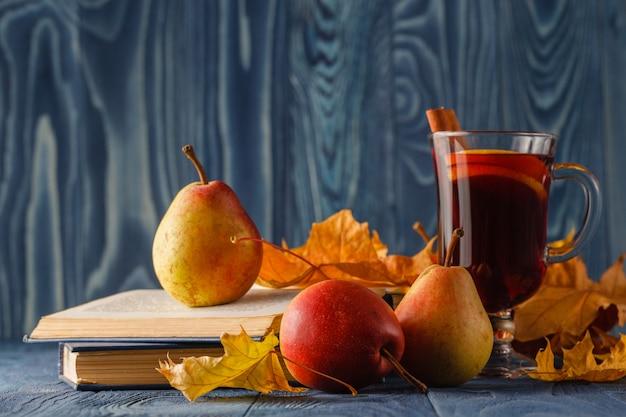 Herfststilleven: glühwein met kaneel, peer, herfstbladeren, boeken en appel op een houten achtergrond