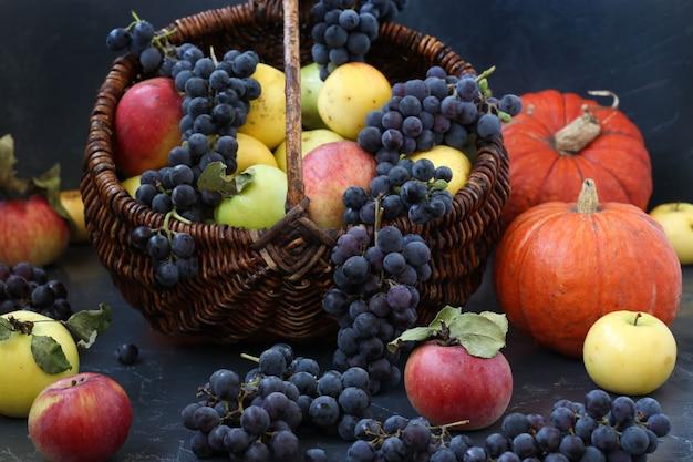 Herfststilleven met appels, druiven en pompoen