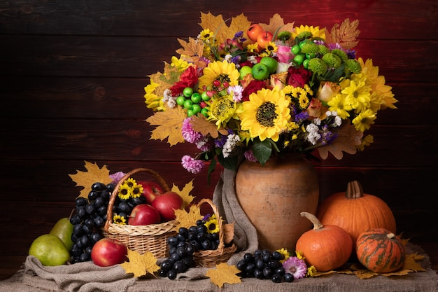 Herfststilleven met blad, zonnebloemen, pompoen en fruit.