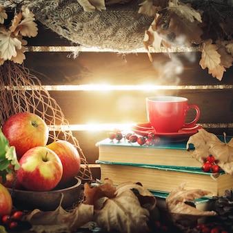 Herfststilleven met een kopje koffie, appels en herfstbladeren.
