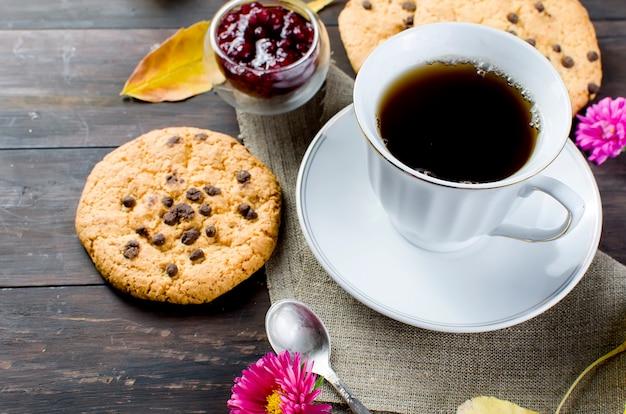 Herfststilleven met kopje thee, koekje en bladeren.