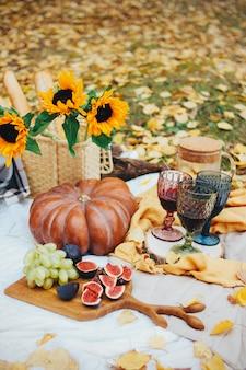 Herfststilleven met pompoen, vijgen en zonnebloemen. picknick in gele bladeren