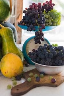 Herfststilleven met pompoenen en druiven op de weegschaal en in een metalen kom op een houten witte tafel. herfstoogst concept.