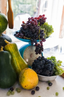 Herfststilleven met pompoenen, meloenen, watermeloen, druiven op een schaal en in een metalen kom op een houten witte tafel. herfstoogst concept.