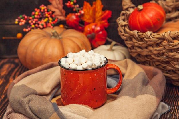 Herfststilleven op een houten ondergrond met cacaomok en marshmallows, geruite sjaal, pompoenen, bladeren